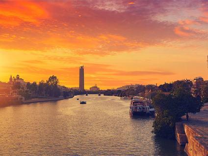 Atardecer en el Guadalquivir con la Torre del Oro de Sevilla a la derecha