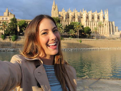 Girl taking a selfie in front of the Palma de Mallorca Cathedral