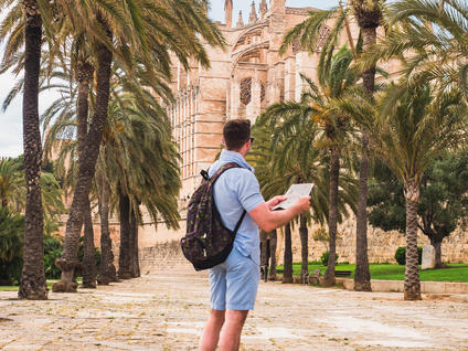 Man with a map standing in front of the Cathedral of Palma de Mallorca, Spain